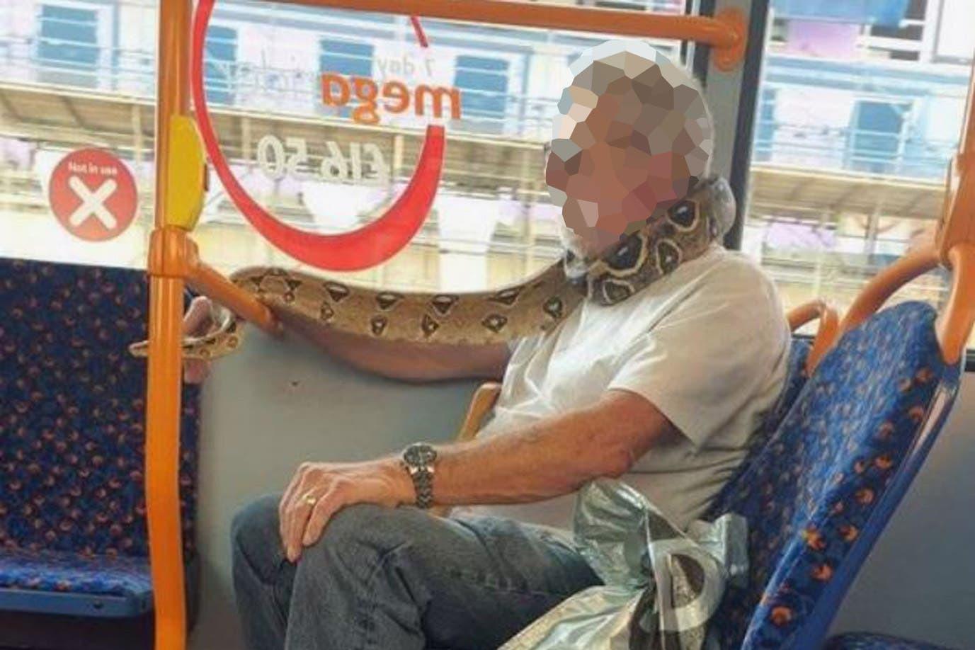 Bărbat, fotografiat cu un șarpe pe post de mască într-un autobuz